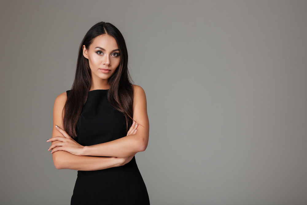 Portrait of a beautiful classy woman in black dress standing with arms folded isolated on a gray background