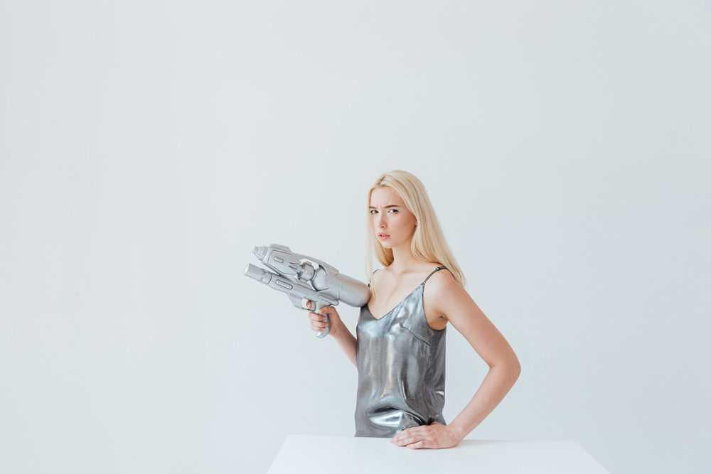 Portrait of a beautiful pensive blonde girl in silver shiny dress holding blaster isolated on the grey background