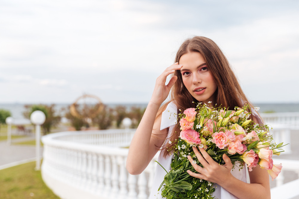 Portrait of a beautiful young girl holding a bouquet of flowers standing on a terrace outdoors