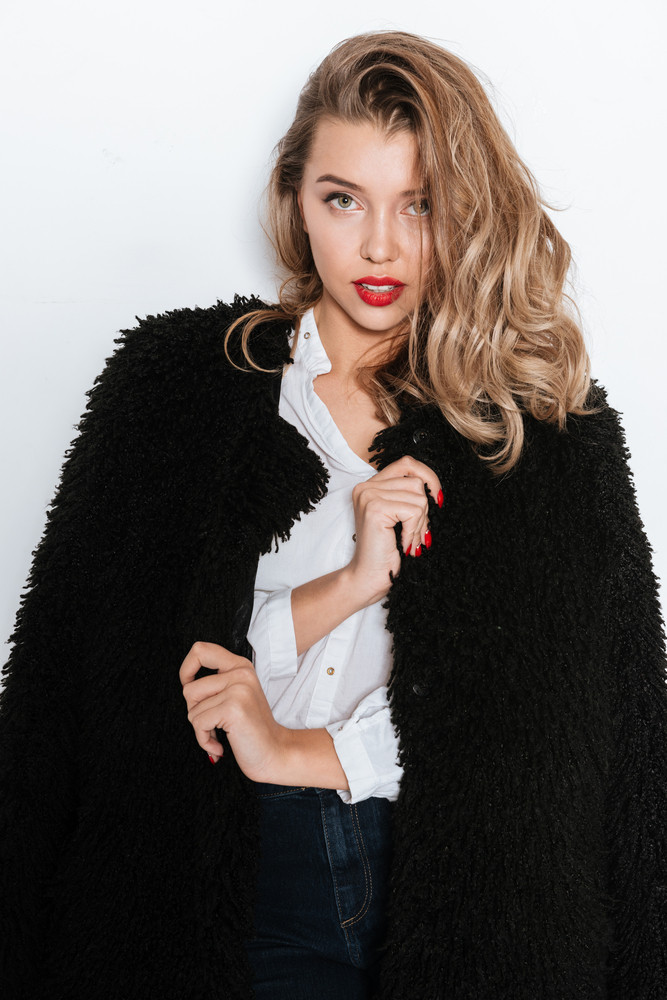Portrait of a beautiful young woman in fur coat standing and looking at camera on white background