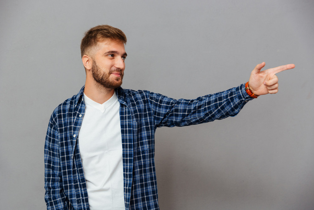 Portrait of a casual bearded man pointing finger away isolated on a gray background