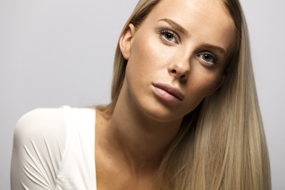 Portrait of a casual blonde woman in white top