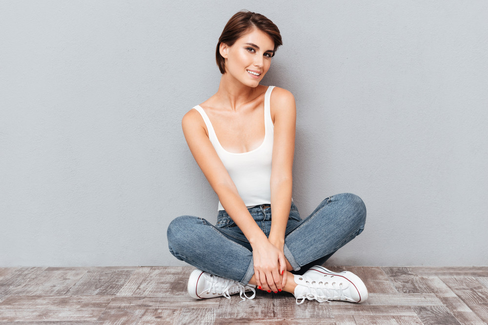 Portrait of a casual happy woman sitting on the floor with legs crossed over gray background