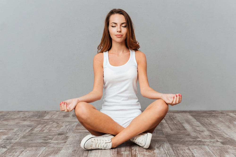 Portrait of a casual pretty woman meditating on the floor on gray background