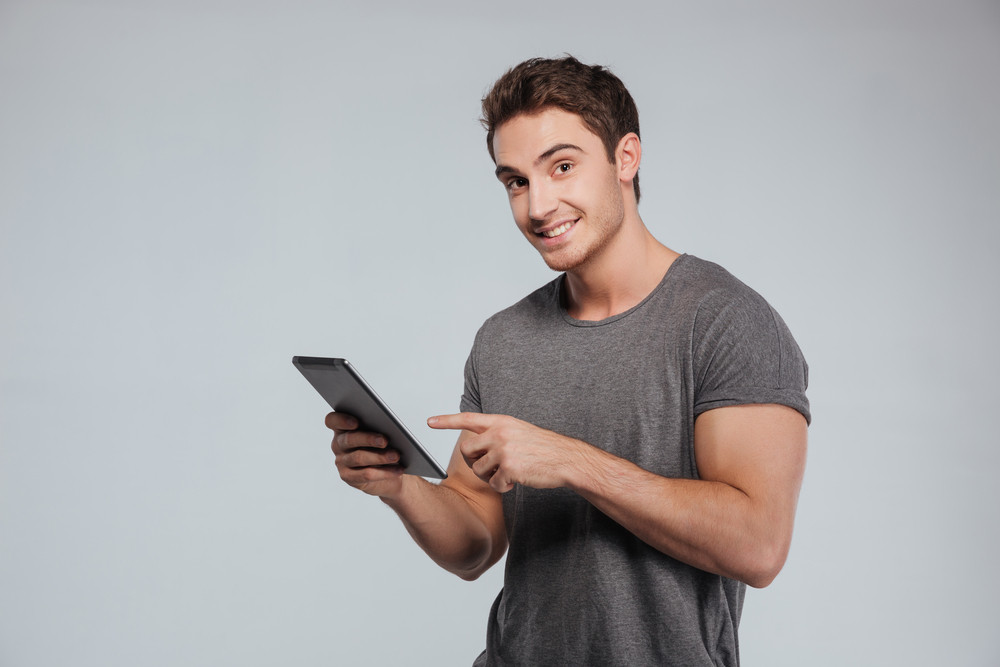 Portrait of a casual smiling man pointing finger at tablet computer and looking at camera over white background