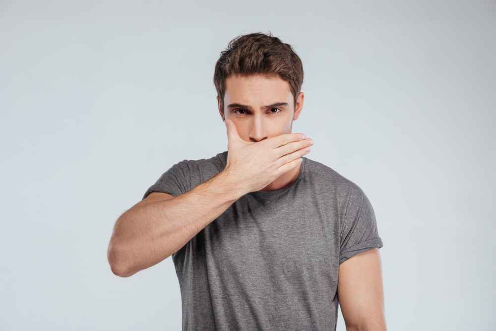 Portrait of a casual young man covering face with one hand isolated on the gray background