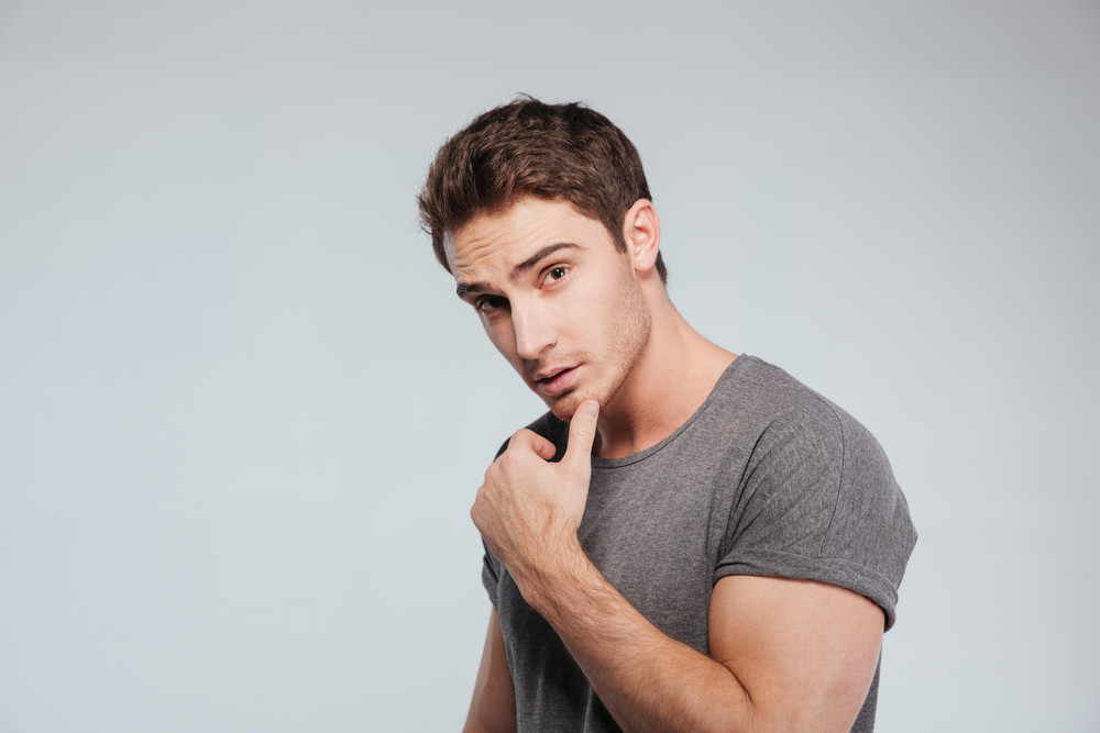 Portrait of a charming brunette man looking at camera over white background