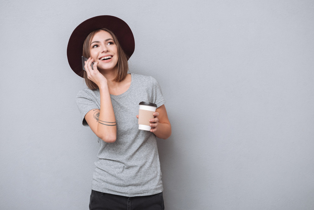 Portrait of a charming young woman in hat speaking on mobile phone while drinking coffee isolated on a gray background
