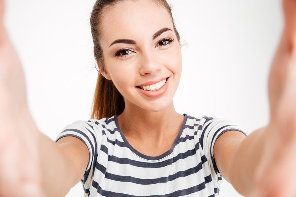 Portrait of a cheerful attractive woman making selfie photo over white background