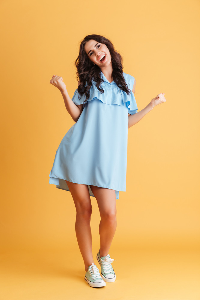 Portrait of a cheerful woman in blue dress celebrating her success over orange background