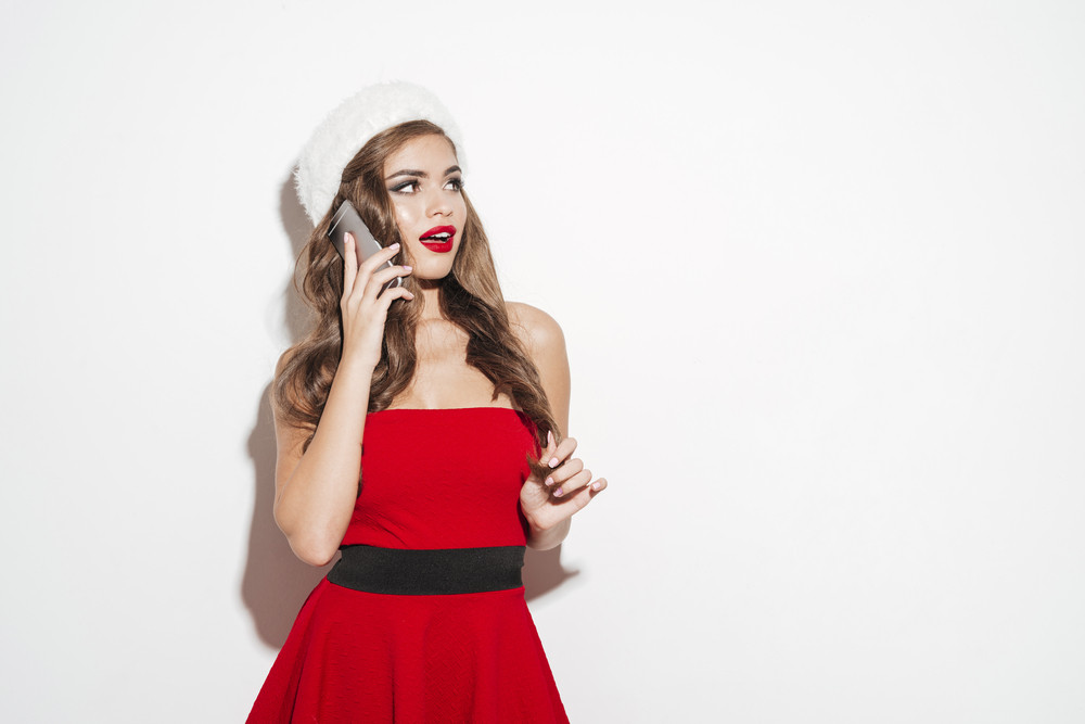 Portrait of a cheerful young woman in red dress talking on mobile phone and looking away isolated on the white background