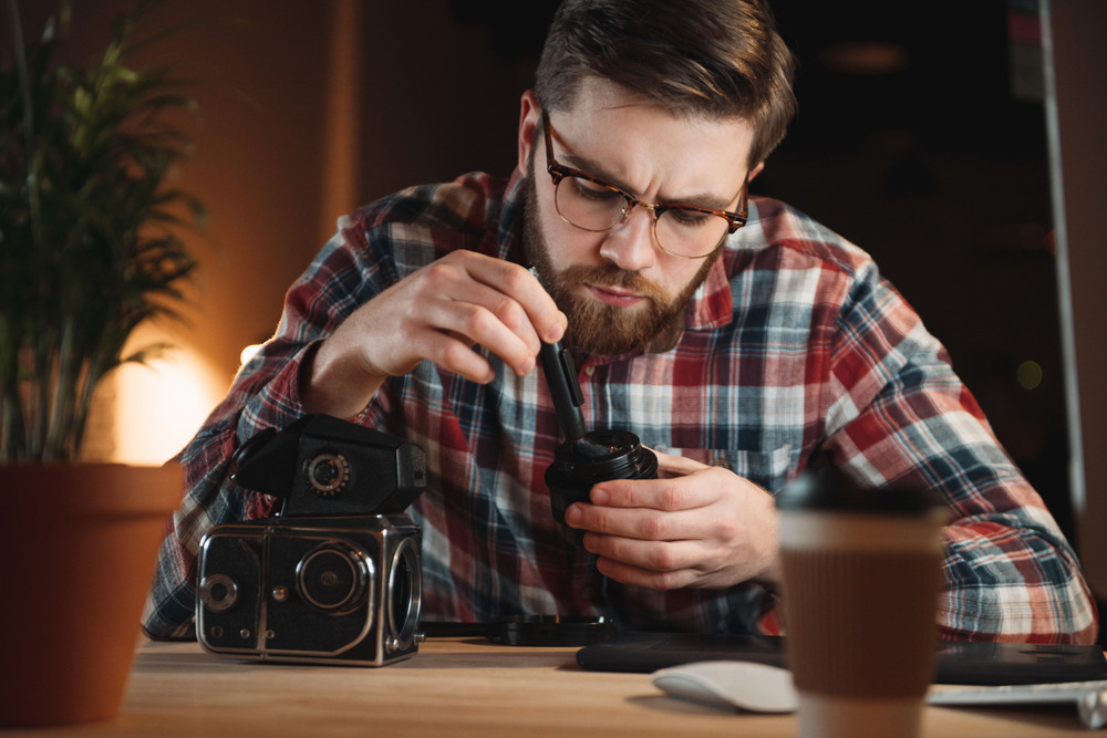Portrait of a concentrated young man repairing an old camera at his workplace