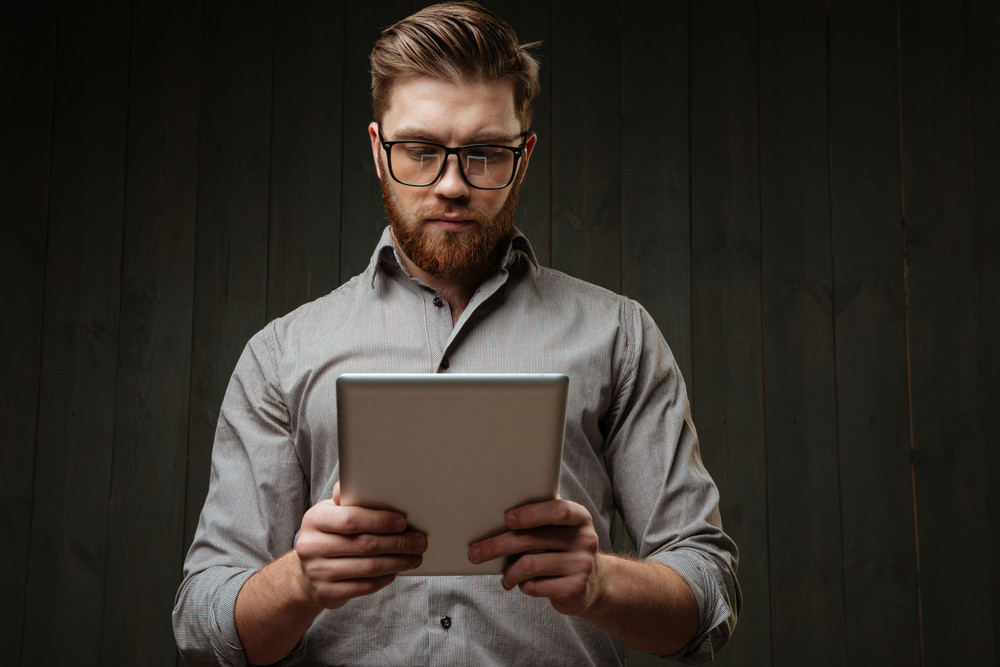 Portrait of a concetrated bearded man in eyeglasses and shirt using tablet computer isolated on the black wooden background