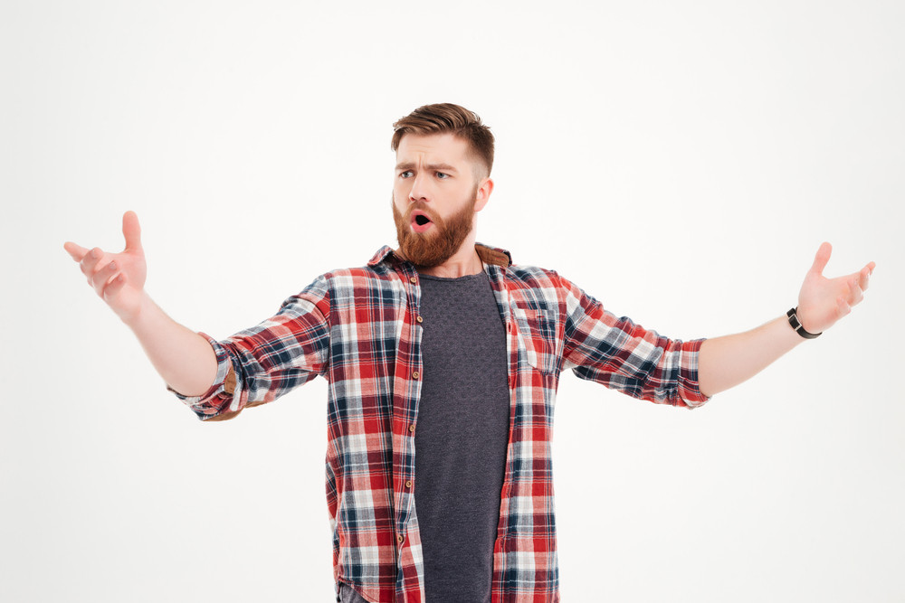 Portrait of a confident bearded man in plaid shirt singing with arms raised isolated on a white background