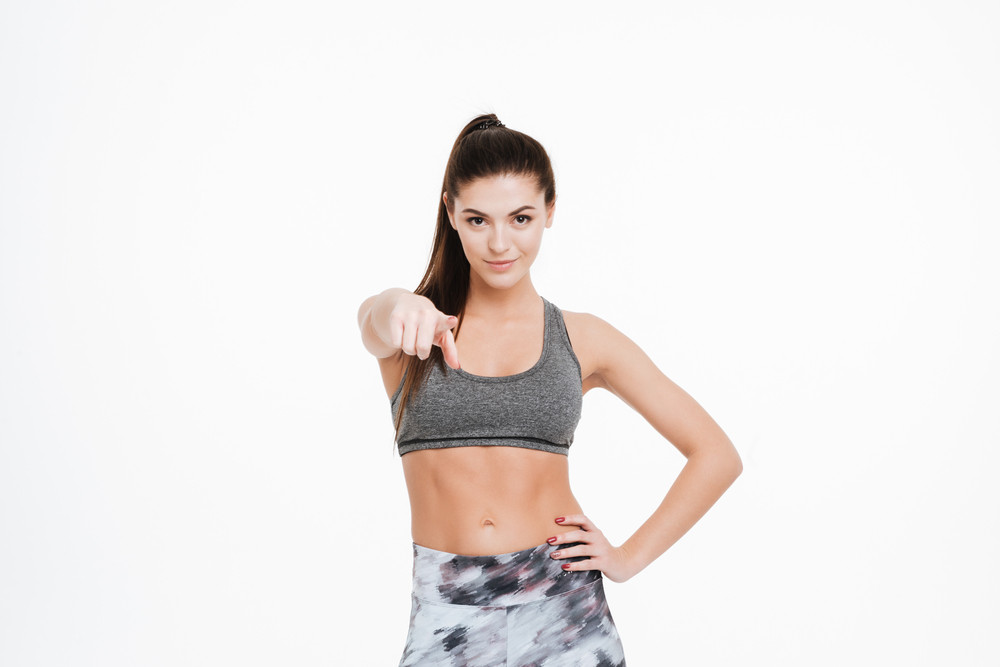 Portrait of a confident fitness woman pointing finger at camera isolated on a white background