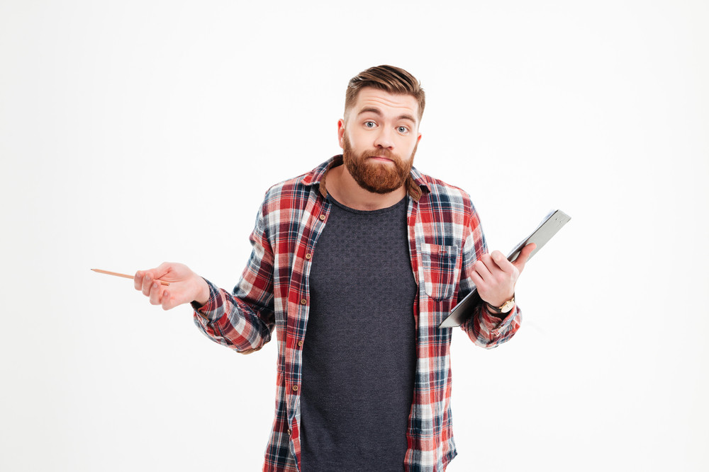 Portrait of a confused bearded man shrugging shoulders and holding clipboard isolated on a white background