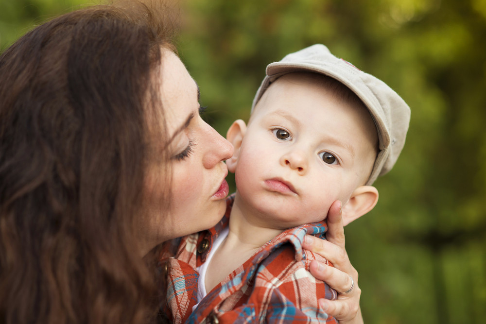 Portrait of a crying little boy who is being held by her mother, outdoors