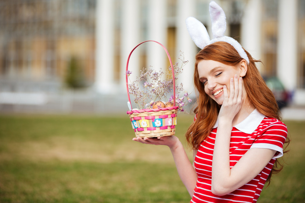 Portrait of a cute smiling red head girl with closed eyes holding easter basket with eggs while sitting in park