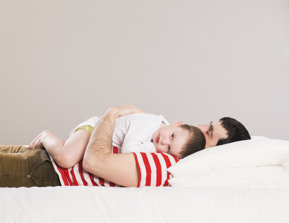 Portrait of a father with his son in bed