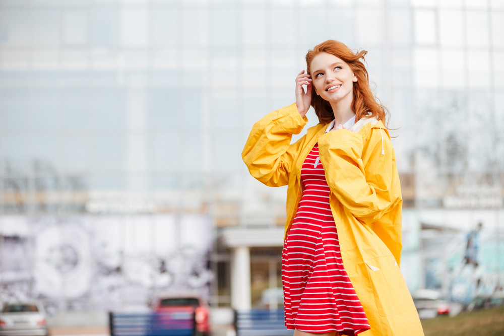 Portrait of a friendly pretty ginger hair girl in coat standing and posing outdoors