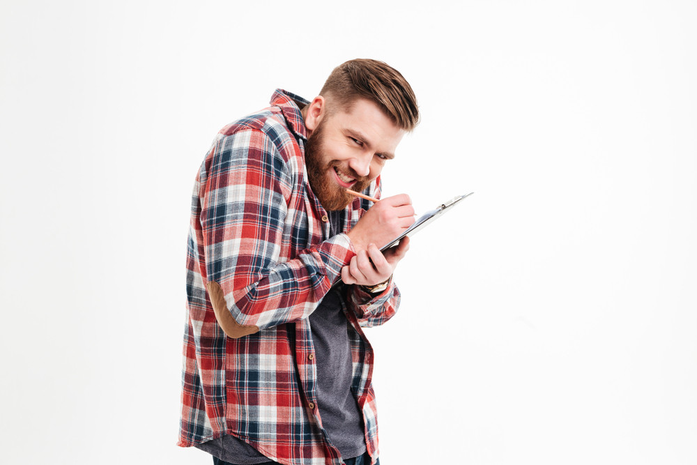 Portrait of a funny bearded man writing notes on clipboard and looking at camera isolated on a white background