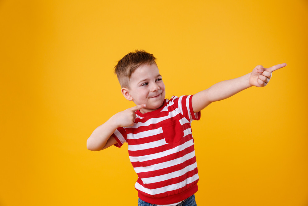 Portrait of a funny little kid pointing fingers away isolated over orange background