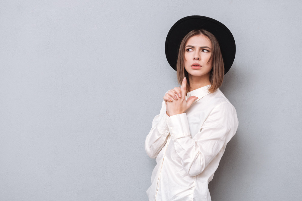 Portrait of a funny serious girl in hat making gun gesture and looking away over gray background