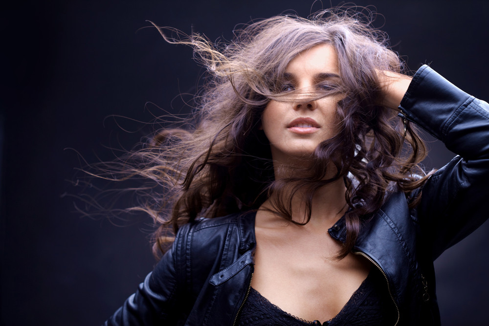 Portrait of a girl with streaming hair against black background
