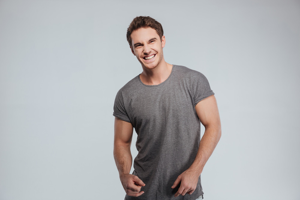 Portrait of a handsome casual man standing and laughing over white background
