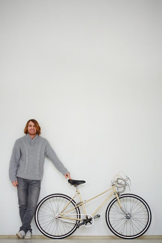 Portrait of a handsome man with bicycle in isolation