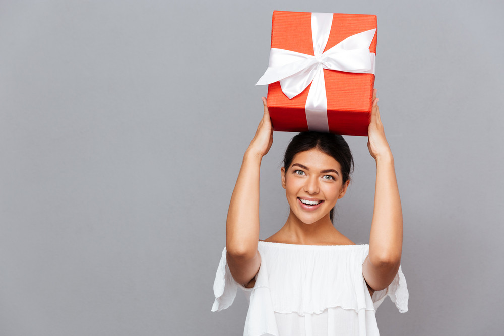 Portrait of a happy amazed woman with gift box on head looking at camera isolated on a gray background