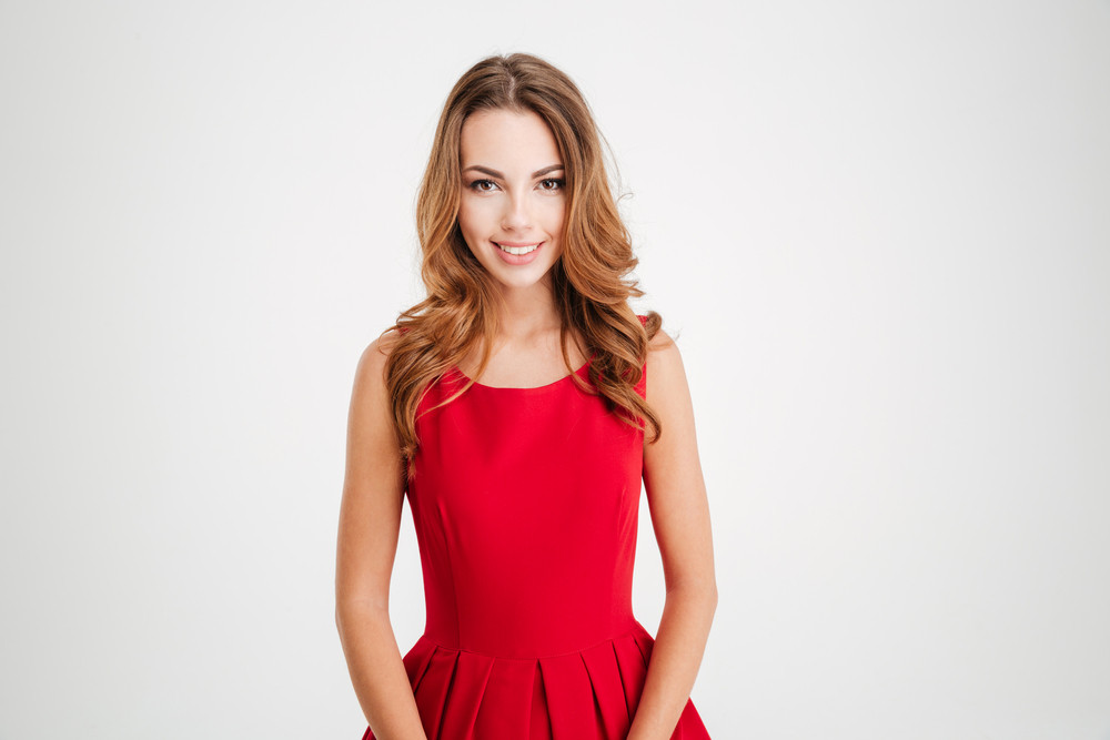 Portrait of a happy attractive young woman in red santa claus costume isolated over white background