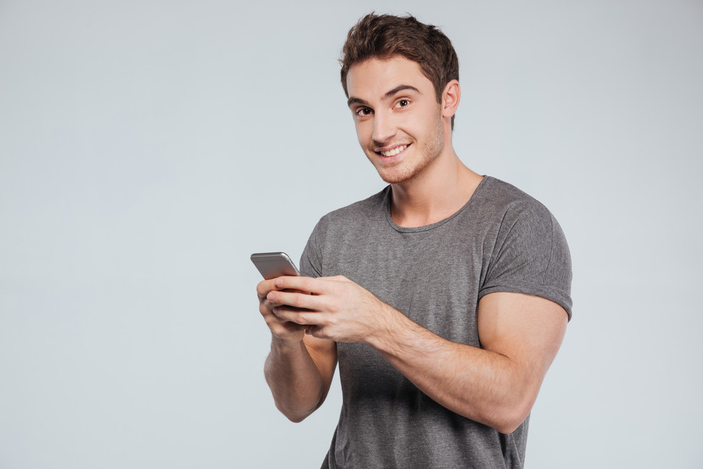 Portrait of a happy casual man using smartphone isolated on a white background