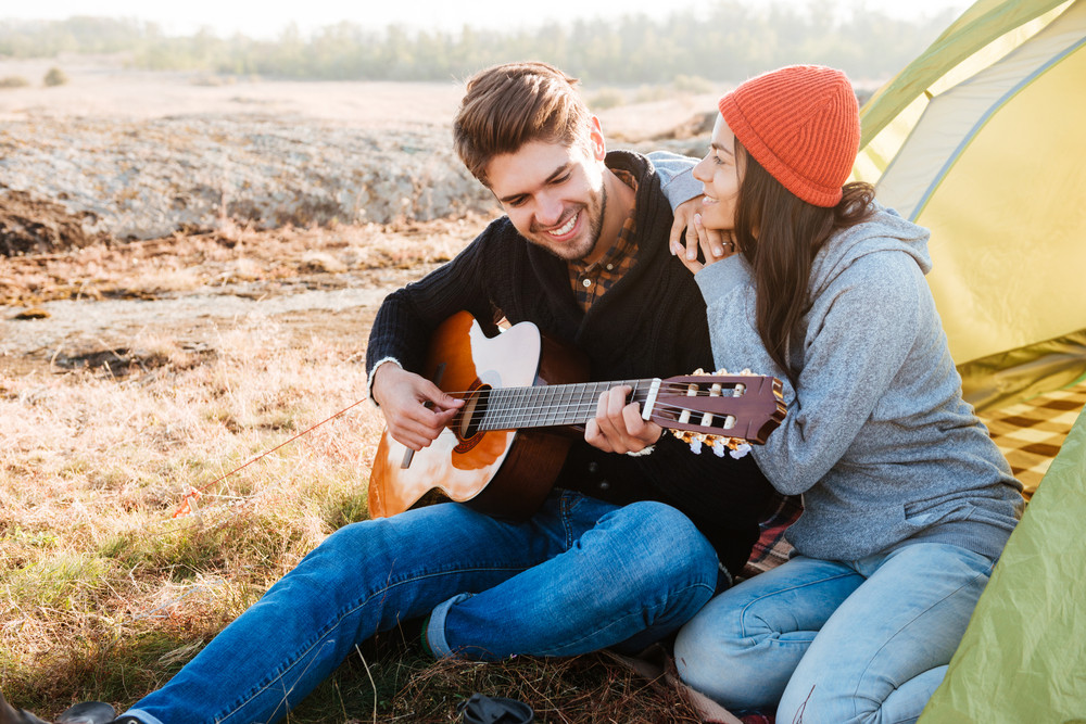 Portrait of a happy couople with guitar having camping with tent outdoors