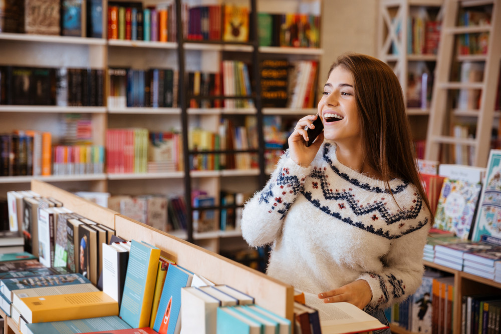 Portrait of a happy laughing woman talking on mobile phone while sitting in library