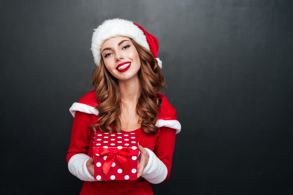 Portrait of a happy lovely woman in red christmas outfit holding gift box isolated on a black background