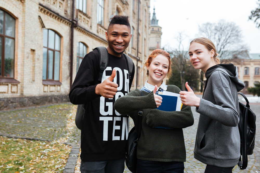 Portrait of a happy multiethnic students standing in university campus and showing thumbs up