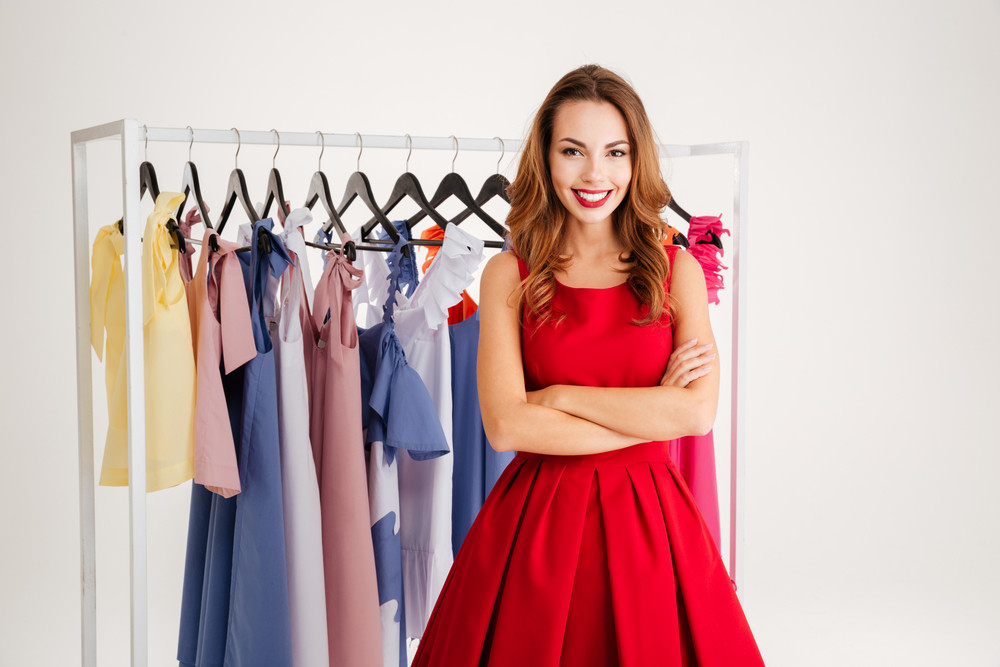Portrait of a happy pretty woman standing at the rack with colorful clothes isolated on a white background