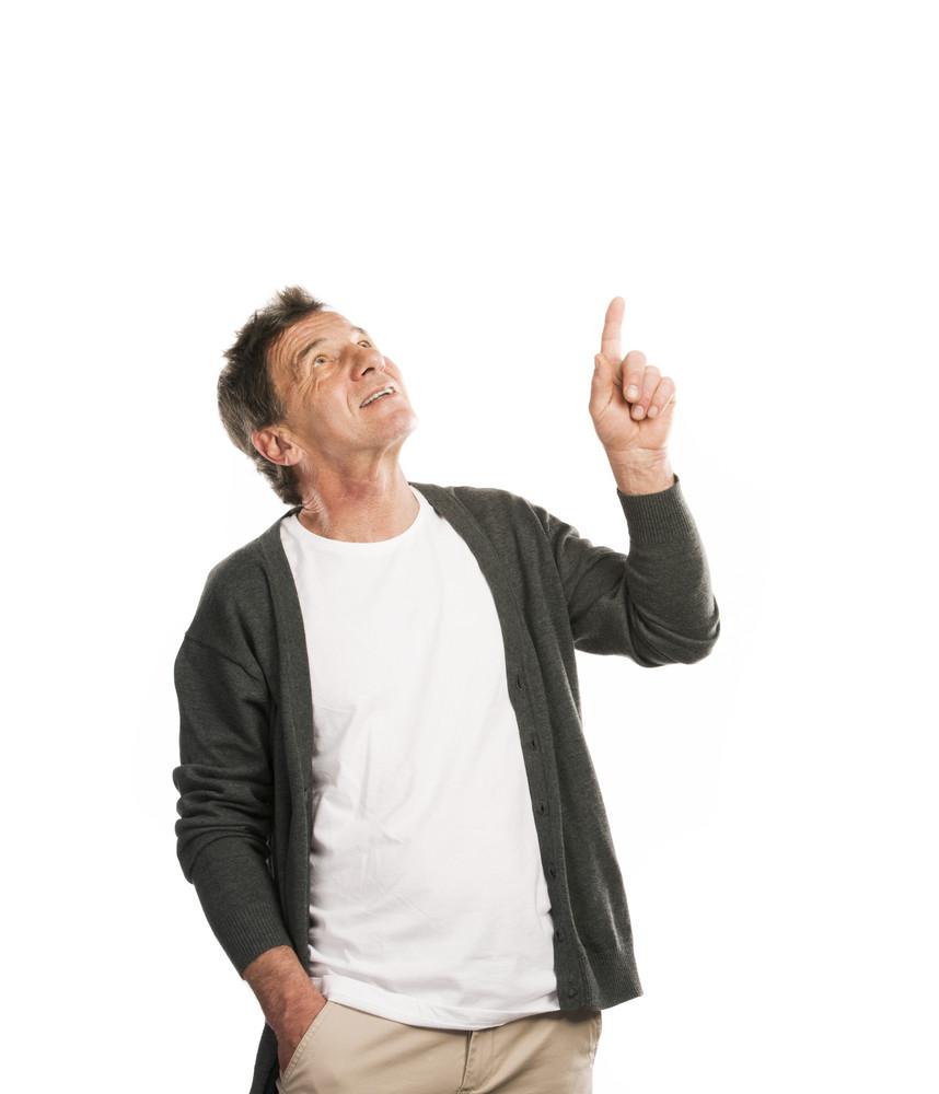 Portrait of a happy senior man pointing upwards isolated on white background