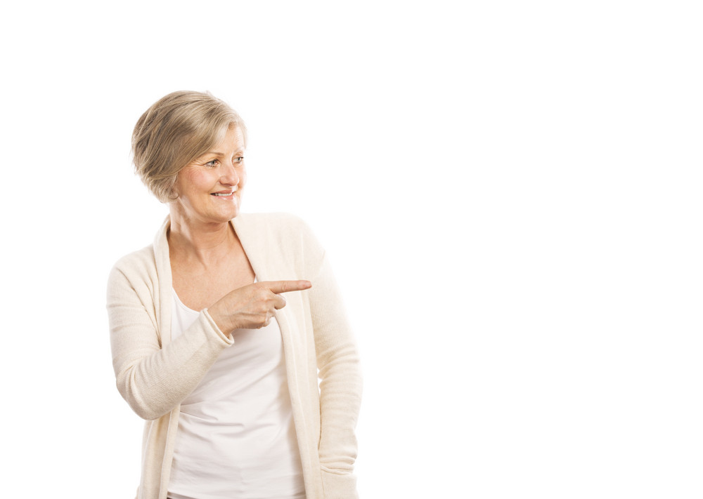 Portrait of a happy senior woman pointing to empty copy space, isolated on a white background