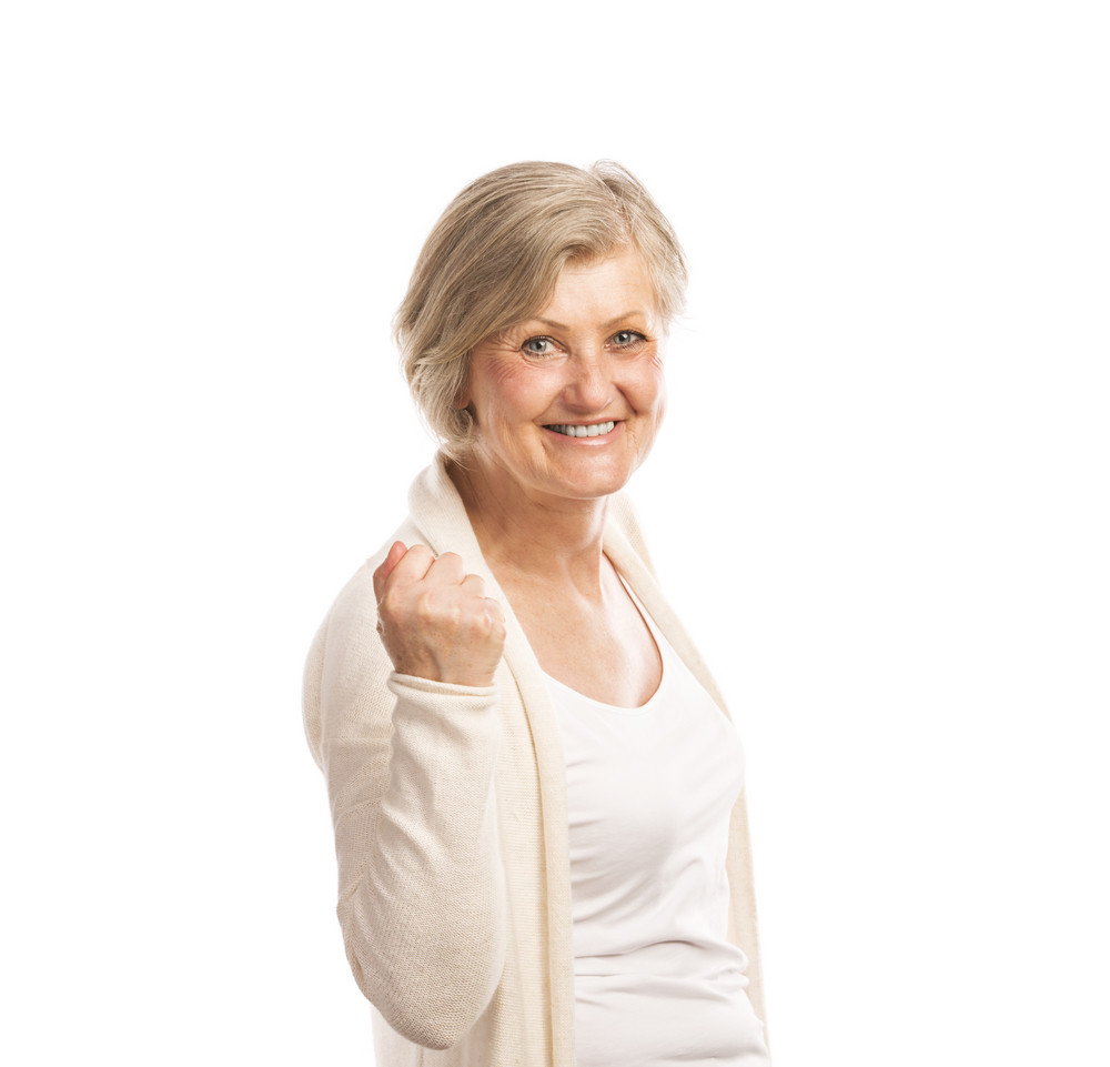 Portrait of a happy senior woman saying yes and gesturing while isolated on white background
