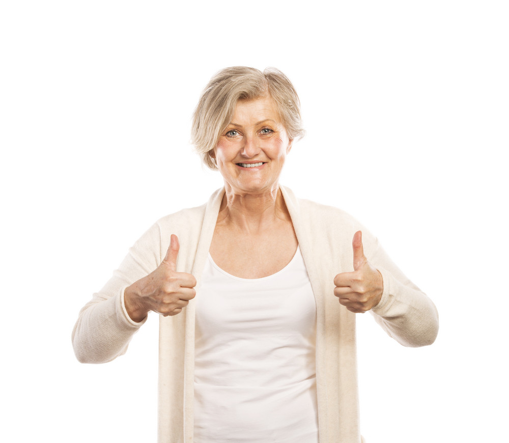 Portrait of a happy senior woman with thumbs up isolated on white background