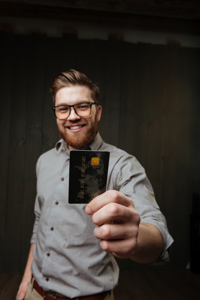 Portrait of a happy smiling bearded man in eyeglasses showing credit card on camera isolated on the black wooden background