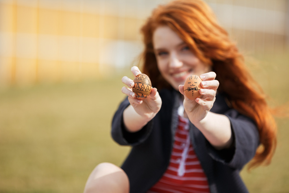 Portrait of a happy smiling girl with long ginger hair showing two painted easter eggs outdoors, focus on eggs