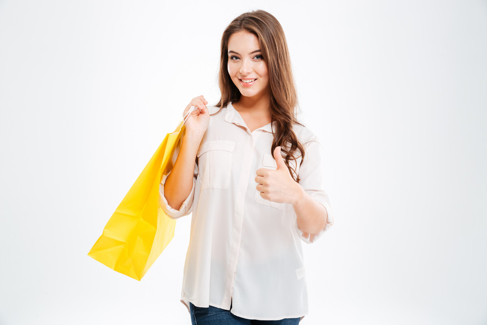 Portrait of a happy woman holding shopping bags and showing thumb up isolated on a white background