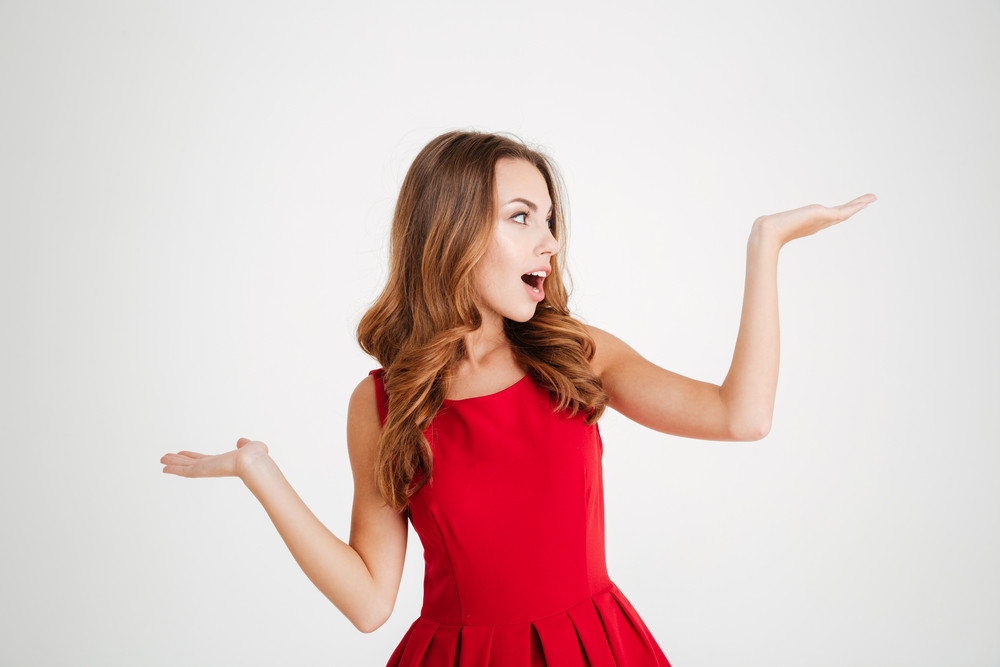 Portrait of a happy young brunette woman in red santa claus dress holding copyspace on two palms over white background