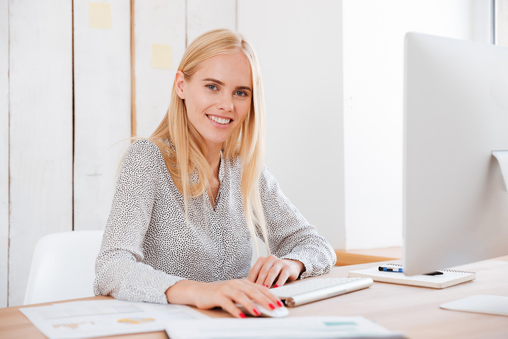 Portrait of a happy young business woman sitting with computer in office