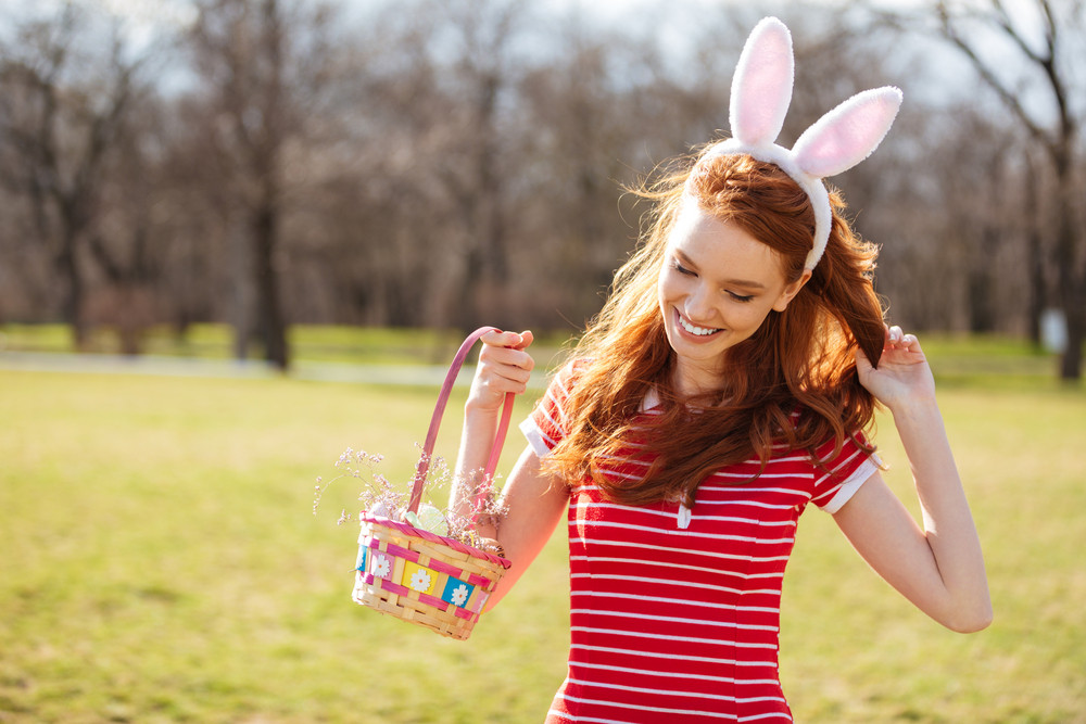 Portrait of a happy young woman with long red hair holding basket with painted eggs and celebrating easter holiday outdoors