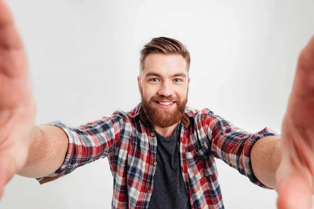 Portrait of a joyful casual man taking selfie and holding camera with hands over white background