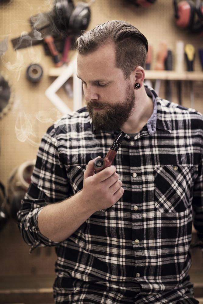 Portrait of a man smoking pipe in wood workshop